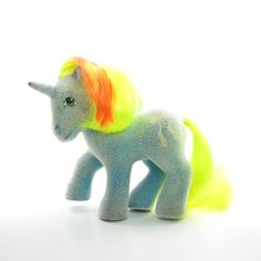 This vintage G1 My Little Pony is Ribbon, she's one of the So Soft Ponies from Year 4 and has white flocking all over her body. Ribbon is a turquoise blue unicorn with a neon yellow tail, and her mane