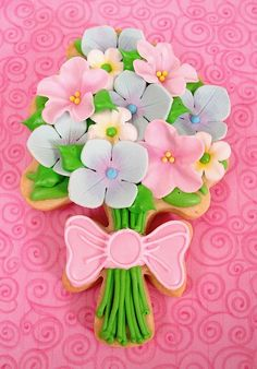 Bouquet Cookie    I got a new shipment of cutters from Ecrandal and a slow week, so its a perfect time to play with my new toys! I really like this bouquet cutter. The stems, leaves and bow are royal icing, and the flowers are fondant.