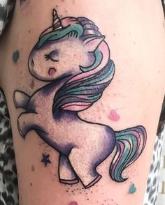 A really cute looking unicorn tattoo. The unicorn is drawn in a somewhat chibi-like fashion. The various colors on the unicorn also add to the cuteness.