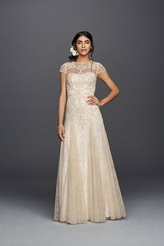 The golden embroidery on Melissa Sweet's lace sheath wedding dress was inspired by a trip to Morocco. Designed with illusion cap sleeves and an airy godet skirt. Exclusively at David's Bridal.