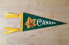 Dark green with yellow, Canada in white and a yellow and orange maple leaf. This small souvenir pennant measures 15 long x (at widest) In good condition with no tears or holes, very slight wrinkle at tip. Orange, Yellow, Canada, Leaves, Bedroom, Green, Vintage, Souvenir, Bed Room