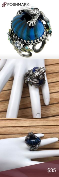 Vintage Frog on Blue Stone Ring Our entire collection of chunky vintage style rings has been a style in our NY boutique. Everyone loves a unique piece! This ring has a large round striated blue glass stone with a little frog sitting on it in antiqued silver finished metal. The sides of this ring are rich in detail and this ring is adjustable. ( fits 6.5-9).  Swarovski crystal accents Antiqued silver finished metal Adjustable band Jewelry Rings