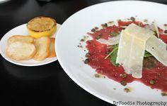 Classically presented Beef Carpaccio:  Slivered Tenderloin, Parmigiano Reggiano, Truffle Vinaigrette, Arugula, and Capers. The Tasting Room in Frederick, MD