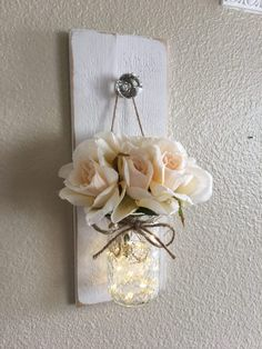 This is my take on a farmhouse chic wall sconce. It is so simple and shabby but at the same time very elegant. It measures 14 long and 5.5 wide, it includes one hanging mason jar with a string of fairy lights. Flowers are included. Please leave me a note at checkout with your