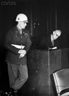 An Allied military policeman leans against the wooden wall of the cabin in which Joachim von Ribbentrop, former Reich Minister of the Exterior and one of the major Nazi war criminals tried in the Nuremberg Trials, sits during the hearings of the Nuremberg Trials in the context of the International Military Tribunal in the Justice Palace in Nuremberg, Germany, in 1946. Photo: Yevgeny Khaldei