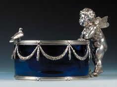 A silver-mounted glass Dish marked Fabergé with Imperial warrant, workmaster Julius Rappoport, St. Petersburg, circa 1890, with scratched inventory number 22305 The circular blue glass bowl with silver mounts of tied reeded bands with suspended tied laurel garlands, one side with the cast, chased and engraved figure of a Cherub with a folded cloth, the opposite with the figure of a dove, marked under base and on upper mount.
