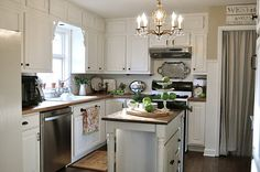 2 smart ideas.  1. Install faux cabinet doors/trim on a bulkhead you can't remove to give the illusion of cabinets going all the way to the ceiling.  2. Install a towel bar on the cabinet at the sink.  Painted cabinets, butcher block island countertop.