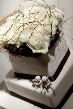 White tiered wedding cake with gold accents and white rose topper, photo Greg Lumley Photography