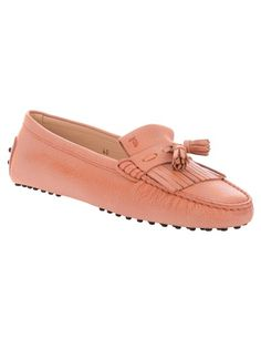 Orange leather loafer from Tod's featuring a round toe, a fringe and tassel detail at the front, a pebbled rubber sole and a rubber studded back section.