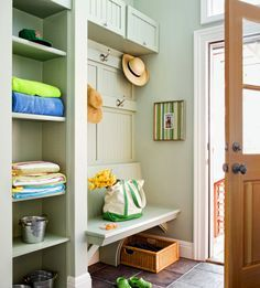 An awkward entry gains practical charm with a tower of open shelves, top cabinets, and a built-in bench, all knit together by a soft shade of green.