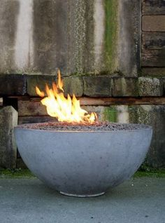 DIY concrete fire pit bowl from eHow.  Summary:  Make sand 'hill' in size you want bowl to be and, using a trowel, cover sand with layers of concrete, smooth a flat bottom to sit it on and vent holes, letting dry slowly under plastic sheet. Invert when dry and voila!