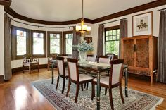 1912 Tudor in Berkeley   In the home's formal dining room, there is a curved wall of windows with small stained-glass panes in the center of each. Photo: Liz Rusby