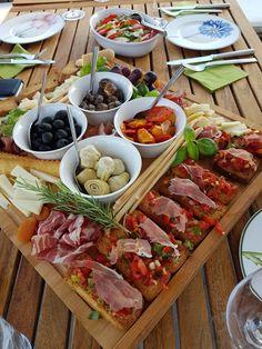 Italian antipasti. Proscutto,  italian cheese, grissini, bruscetta, artichoke-hearts, Black olives, marinated mushrooms, grapes, grilles peppers and dried apricoses.