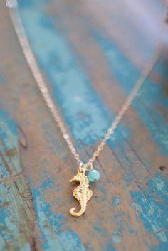 Este collar es poner una cadena de oro. El colgante en la parte inferior es un caballito de mar dorado con un cordón azul Unido a él. Este collar es faltar un colgante más grande.