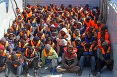 North-African immigrants sit in an Italian Navy's amphibious vessel as they are brought to the Italian Navy ship 'San Giorgio' after being rescued at sea off the coast of Libya
