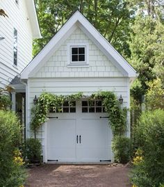A single carriage house garage door is further embellished with creeping vines. Carriage House Garage Doors, Diy Garage Door, Garage Exterior, Carriage Doors, Garage Door Design, House Doors, Car Garage, White Exterior Houses, Dream House Exterior