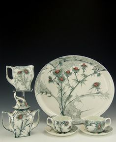 Rozenburg, Den Haag, Samuel Schellink, 1900: a rare eggshell porcelain tête-à-tête service, comprising a large tray, a sugar basin with plumed cover, cream jug,and two cups and saucers. All decorated wit flowering thistles in shaded of old rose, brown, green and a dark green-blue.