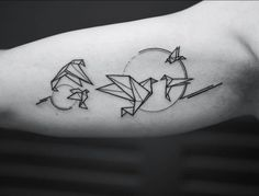 Origami bird tattoos on the right inner arm.