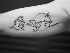 Origami bird tattoos on the right inner arm.