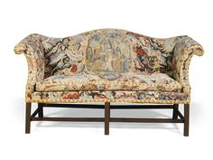 A mahogany sofa covered with needlework with an arched back and scroll arms covered with associated mid 18th century, gros-point and petit-point needlework, on carved square legs with stretcher