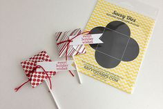 """Individual treat or party favor on a stick wrapping. Die cut a square envelope using Savvy's die. Make a hole using a 1/8"""" hole punch in the center of the fold on one of the flaps. Insert a flat sucker. Fold the flaps so they overlap and then add a touch of ribbon or baker's string. Attach a little banner and hand stamp with """"sweet holiday wishes"""" ."""