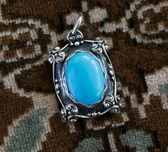This medieval turquoise stone costume pendant from Aleks jewelry is accented by a rich blue stone, in boho style. Silver granules and other textures add interest and frame the stone. The 925s sterling silver has been given a gunmetal grey patina by oxidization and hand finishing, to add depth and mellow character.  The silver used is 100% guaranteed sterling silver, no substitutes. The pendant can be signed by the artist per your request.