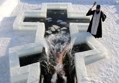 A Belarus Orthodox believer plunges into icy waters as a priest blesses him on the eve of the Epiphany holiday in Pilnitsa some 30 km outside Minsk, on January 18, 2013. Thousands of believers jumpe into holes cut in ice, braving freezing temperatures, on January 18 and early on January 19 to mark Epiphany, when they take part in a baptism ceremony. (Photo by Viktor Drachev/AFP Photo)