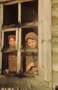 Russian girls glancing at the advancing German soldiers from behind the window of their hut. Photo taken by a German soldier. Autumn of 1941.