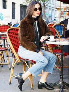 Editorial Director Kat Collings wears a cropped fur jacket, turtleneck, vintage jeans, snake-print booties, and aviator sunglasses