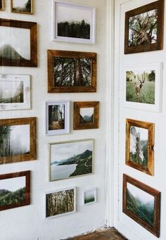 the mix of white and wooden frames feels grounded. love that they're hung all the way to the floor..