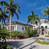 A circular driveway and tall palm trees welcome guests to the entrance of this stately Naples, Fla., home. The 8,299-square-foot house has six bedrooms, 7 baths and 125 feet of beach frontage. The property qualifies for immediate membership eligibility for the Port Royal Club.
