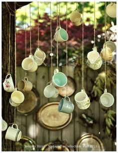 Hanging cups as a curtain. I really want to do this!  I saw this idea in a cafe window in Belgrade using china cups.  It really looked great!