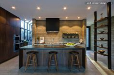 A floor-to-ceiling freestanding shelf delineates the kitchen area without inhibiting its openness and flow. Two floating steel shelves from Henrybuilt were added to the kitchen's board-formed concrete wall, and had the range hood wrapped in the same material to match. The polished concrete floors that run throughout the house were not poured and then scored; they were created in individual sections. When, not if, a crack appears, it can only go so far, this process minimizes repairs.