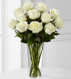 This white rose bouquet is accented with seeded eucalyptus and arranged in a simple glass vase.  Approx. 18H x 12W