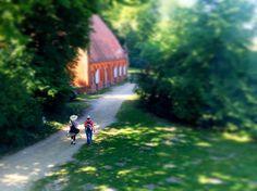 O paraíso é bem pertinho. #paracegover A imagem mostra um casal andando por uma trilha da Ilha dos Pavões, em Berlim. Há uma construção do lado esquerdo onde ficavam os cavalos do Kaiser. Tudo em volta é verde. — at Pfaueninsel Im Wannsee