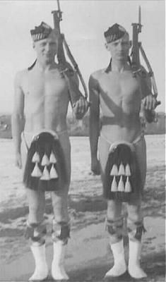 Two Calgary Highlanders stand by the banks of the Bow River, Calgary, before departing for the war. They are humourously depicting Canada's equipment shortages at the beginning of the war... too many volunteers, not enough uniforms!