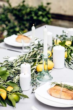 Beautiful Tuscan tablescape with fresh herbs, lemons and candles. And I love the idea of binding fresh rosemary on the individual bread loaves,
