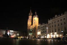 Catedral de Santa Maria em Cracóvia, Polônia. Construída nos anos 1220, a catedral apresenta torres gêmeas concebidas por dois irmãos (uma torre para cada) com a altura máxima de 81 metros. Encontra-se no canto da maior praça de mercado na Europa.  Fotografia: Stuart Spicer no Flickr.