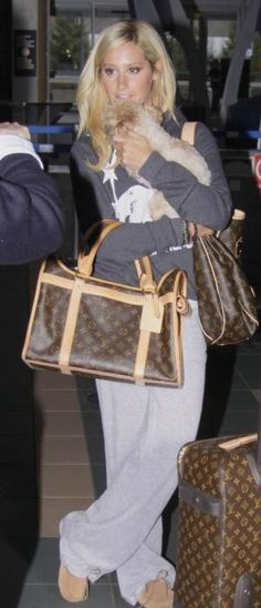 Who made Ashley Tisdale's brown purse, dog carrier, suitcase, tan shoes, gray pants and gray sweatshirt that hse wore at LAX airport, March 15, 2010? Pants – Juicy Couture Velour Snap Pocket  Sweatshirt – Monrow Kangaroo Pocket Pullover Sweatshirt  Purse, suitcause and dog carrier – Louis Vuitton Monogram  Shoes – Ugg Australia Dakota Moccasin Slippers