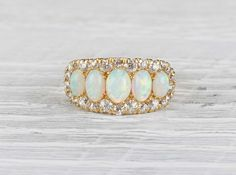 Antique Victorian ring made in 18k yellow gold and set with five oval cabochon opals. Accented with 26 single cut and old European cut diamonds. Circa 1890.