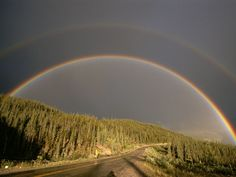 alaska highway rainbow...Like a portal to wild spaces, a double rainbow hangs over the Alaska Highway in British Columbia, Canada.