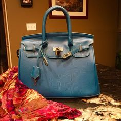 Birkin Style Handbag This bag is just stunning!it is a no brand version of the famous Birkin style bag... For a fraction of the cost! Nice quality vegan leather, four feet on bottom. Comes with clochette and working key. Silver hardware accents the vibrant blue leather. Chocolate brown interior. Gently used condition. This bag is a show stopper! Own that Hollywood style for less!!☺️ Bags Satchels