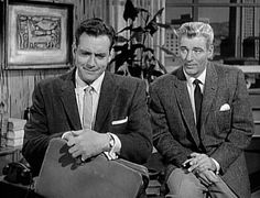 Perry Mason and Paul Drake are sitting in Perry's office on his desk. Perry looks frustrated, Paul looks amused.