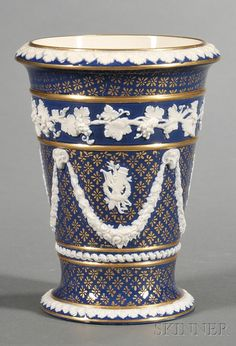 Wedgwood Victoria Ware Vase, England, c. 1890, gilded florets to a dark blue ground on a cream body, trophies within central floral festoons terminating at ram's heads, fruiting grapevine border.
