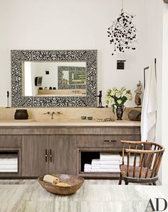 Elegant surfaces predominate in the master bath, with stained-walnut vanities, limestone countertops, and a marble floor | archdigest.com