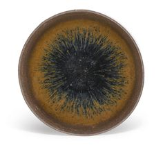 A 'Jian' 'hare's fur' tea bowl, Song dynasty, the slightly rounded sides rising from a short straight foot to an everted rim, covered overall in a rich dark lustrous brown-black glaze with russet hare's fur streaks extending from the rim down the interior and exterior, the glaze falling short of the foot to reveal the dark grey stoneware body 10.8cm., 4 1/4 in.