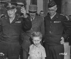 Standing in front of the famous Arc De Triomphe in Paris General Dwight D. Eisenhower addresses cheering Frenchmen. To his left, General Joseph Koenig, Lt. General Omar N. Bradley, centre a happy French child, France, August 27th 1944