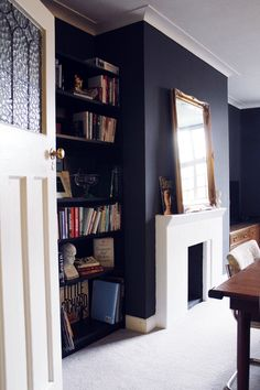 Living room bookshelves, gilt mirror and fireplace.