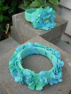 water bottle bracelet- use a water bottle for the bracelet part, wrap old t-shirt or any fabric around plastic, cut out flowers from fabric and glue together-- 100% recycled accessory!