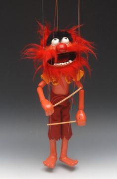 Animal, from the television series The Muppets Show - Pelham Puppets SL Range, large hollow moulded head with painted features, large rounded red nose, wearingA deep orange short jacketAnd burgundy red knee length trousers, holdingA pair of drumsticks in hands, boxed, this puppet was never sold in the USA, late 1970's/early 1980's